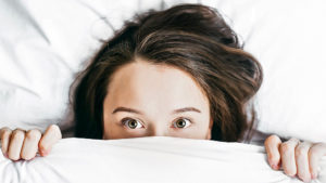 Angst Fehler zu Machen beschrieben mit einer Frau unter einer weißen Decke