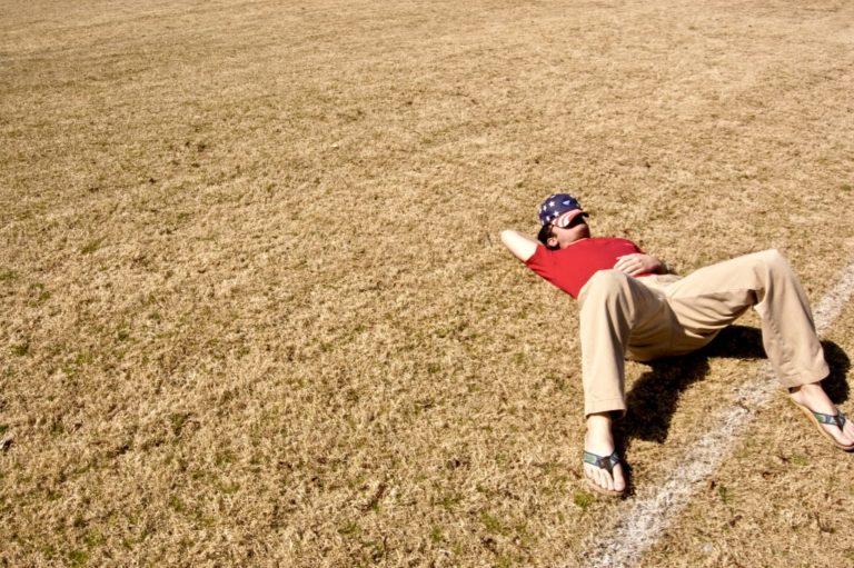 Faulheit überwinden beschrieben durch einen Mann, der auf einer Wiese schläft