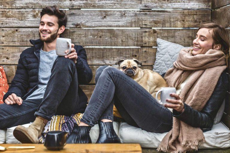 Methoden der Selbstreflexion zwei glückliche Menschen sitzen mit Kaffee und Hund