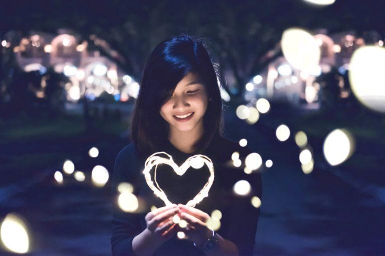 Wie lerne ich mich selbst zu lieben Frau mit leuchtendem Herz