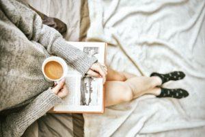 Bücher über Selbstliebe beschrieben durch eine Frau mit einer Kaffeetasse und einem Buch