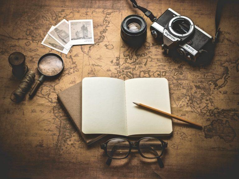 Erfolgsjournal beschrieben durch ein Notizbuch und eine Landkarte