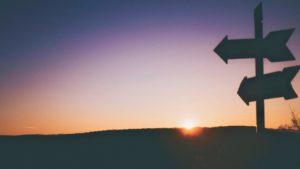 Entscheidungen treffen beschrieben durch Wegweiser im Sonnenuntergang