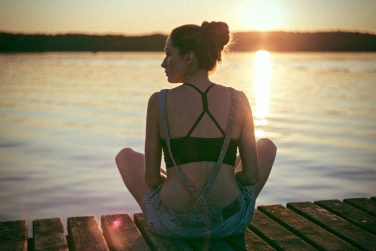 gelassener werden beschrieben durch eine Frau, die auf einem Steg sitzt