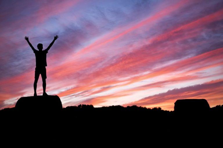 Zu sich selbst finden beschrieben durch einen jungen, der sich freut und in den Sonnenuntergang schaut