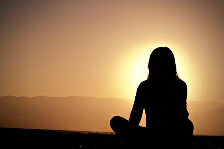 Intuition stärken gezeigt anhand einer Frau, die zur Sonne blickt