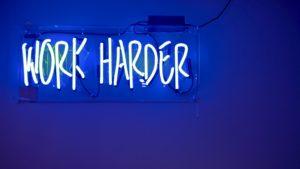 """Perfektionismus ablegen beschrieben durch ein Schild """"work harder"""""""