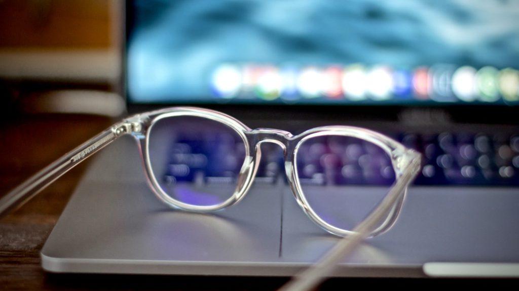 produktiver werden beschrieben durch eine Brille liegend auf einem Laptop