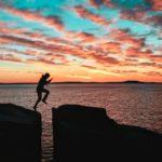Unsicherheit überwinden beschrieben durch einen Mann, der über einen Felsspalt springt
