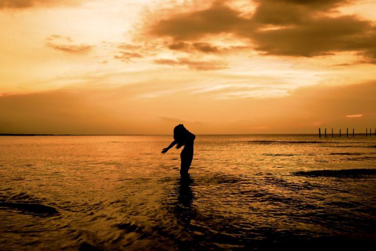 Unsicherheit überwinden beschrieben durch eine Frau, die ihre Arme befreiend zum Himmel ausbreitet