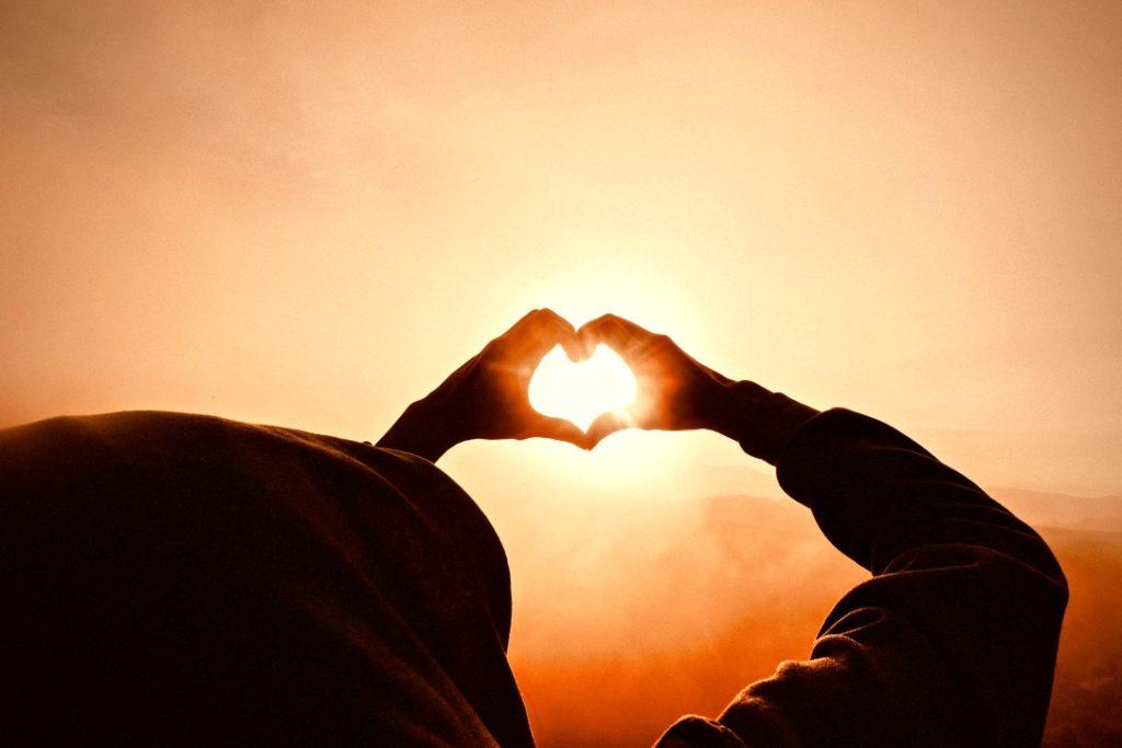 Positives Mindset beschrieben durch eine Person, die mit ihren Händen ein Herz formt