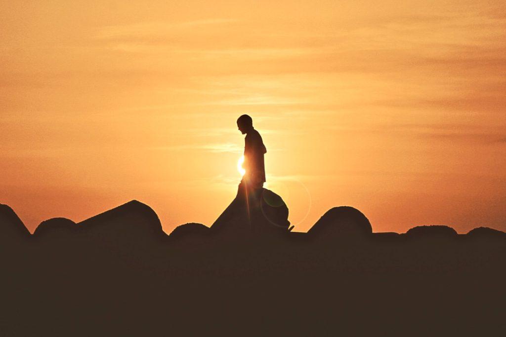 Zu sich selbst stehen und authentischer sein beschrieben durch einen Mann, der im Sonnenuntergang läuft