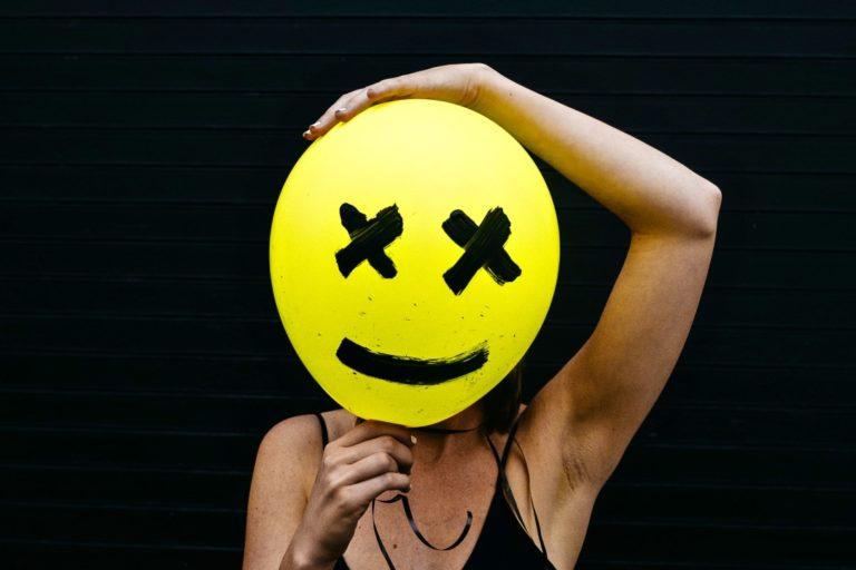 authentischer sein und zu sich selbst stehen beschrieben durch ein Smiley-Balloon, den sich eine Frau vor das Gesicht hält.