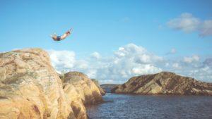 Mutiger werden beschrieben durch einen Mann, der von einer Klippe ins Wasser springt