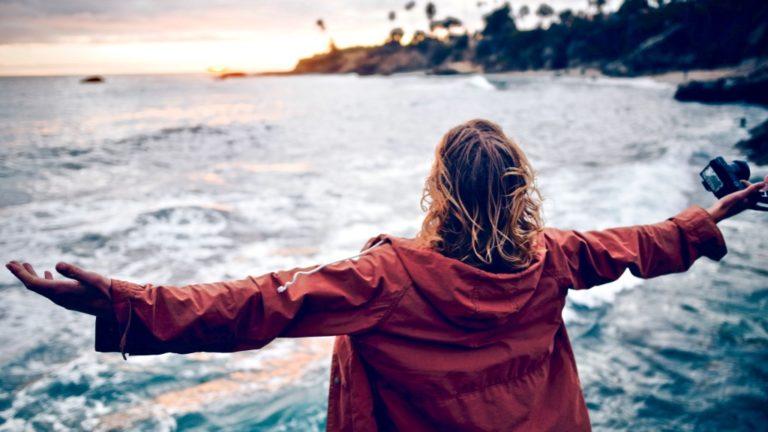 Komfortzone verlassen beschrieben durch eine Frau, die ihre Arme Richtung Meer öffnet
