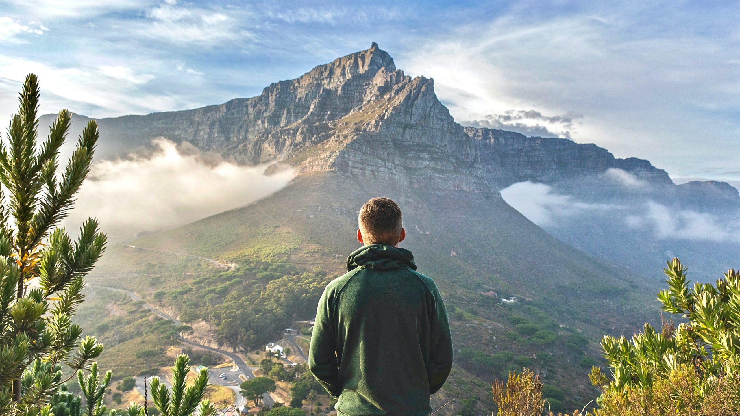 Kopf freibekommen beschrieben durch einen jungen Mann der beruhigt in die Ferne auf einen Berg schaut