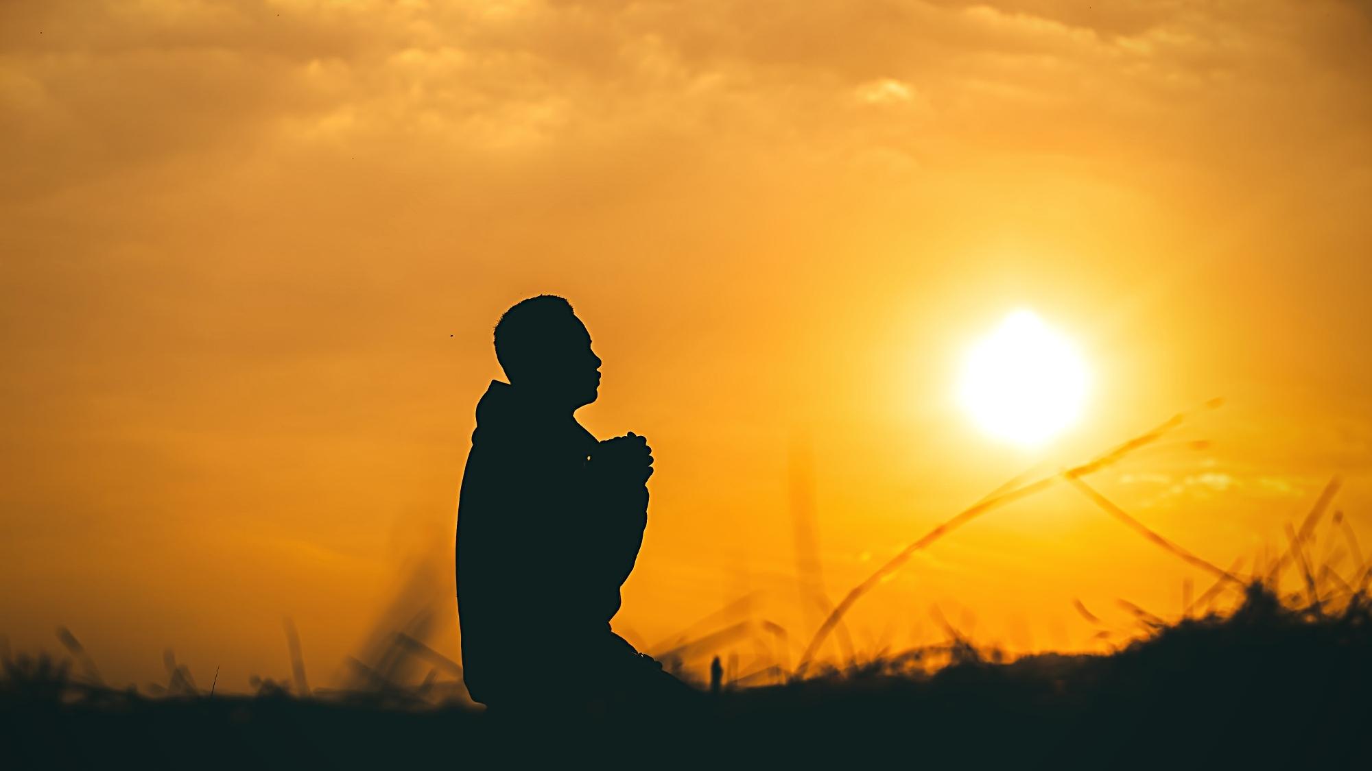 Negative Glaubenssätze auflösen und erkennen beschrieben durch die Silhouette eines Menschen im Sonnenuntergang