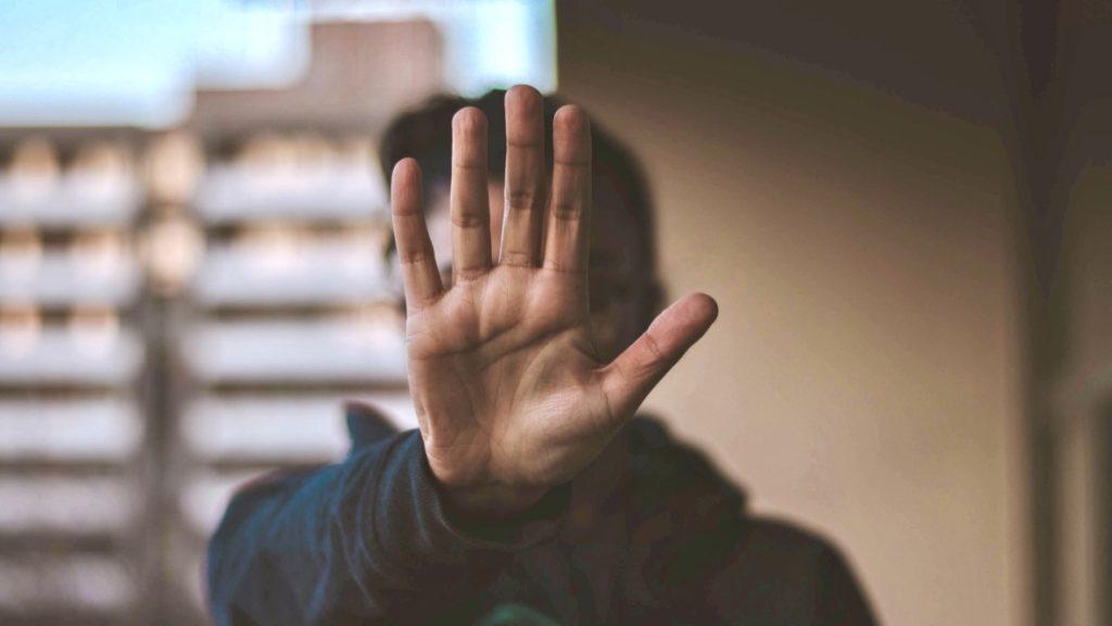 Grenzen setzen anhand eines Menschen, der die Hand vor dem Gesicht ausgestreckt hält